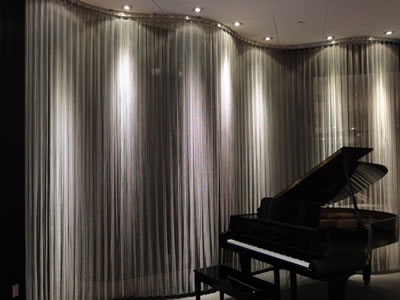 Beside the piano, there is a piece of flat chainmail curtain with curved hanging track as a space divider.