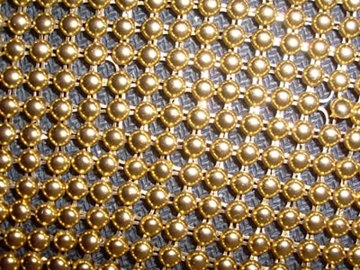 A piece of gold color bead curtain with shiny surface.