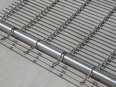 A corner of stainless steel woven wire drapery with hanging rod.