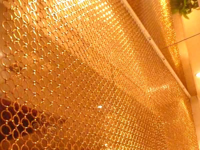 Gold color ring mesh curtain as wall decoration.