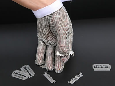 A chainmail glove with a white wrist strap is being carried out anti-cutting test by using a blade.