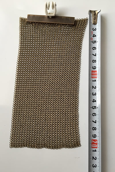 A piece of chainmail curtain is measured by a meter ruler.