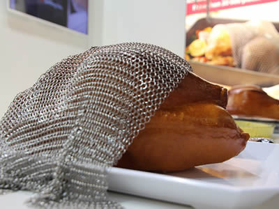 A piece of stainless steel chainmail baking cover is covering a chicken in the plate.