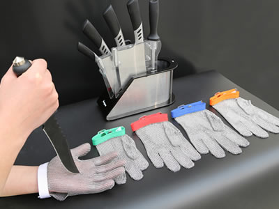 A stainless steel mesh glove with a white wrist strap is being carried out anti-puncturing test.