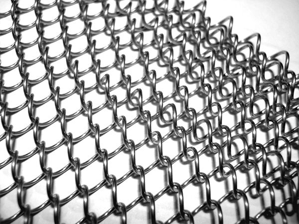 A piece of stainless steel metal coil drapery mesh curtain on white background.