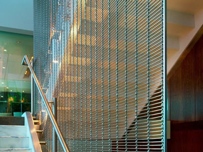 Stainless steel woven wire drapery is installed on stair side